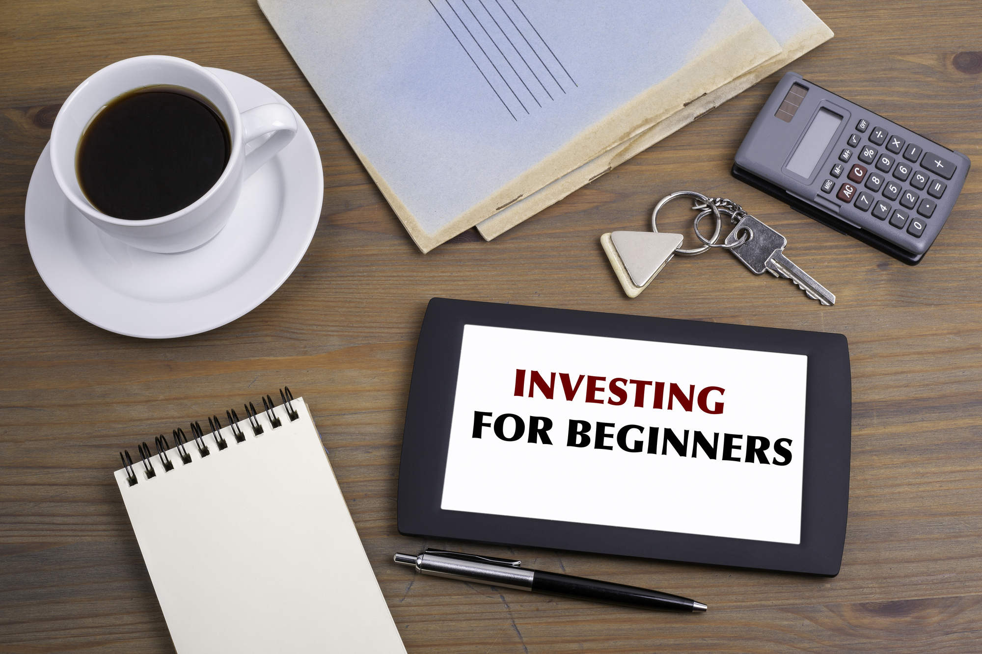 INVESTING FOR BEGINNERS. Text on tablet device on a wooden table